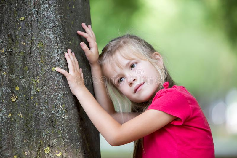 Portrait of a pretty little child girl standing near big tree trunk in summer park outdoors royalty free stock photography