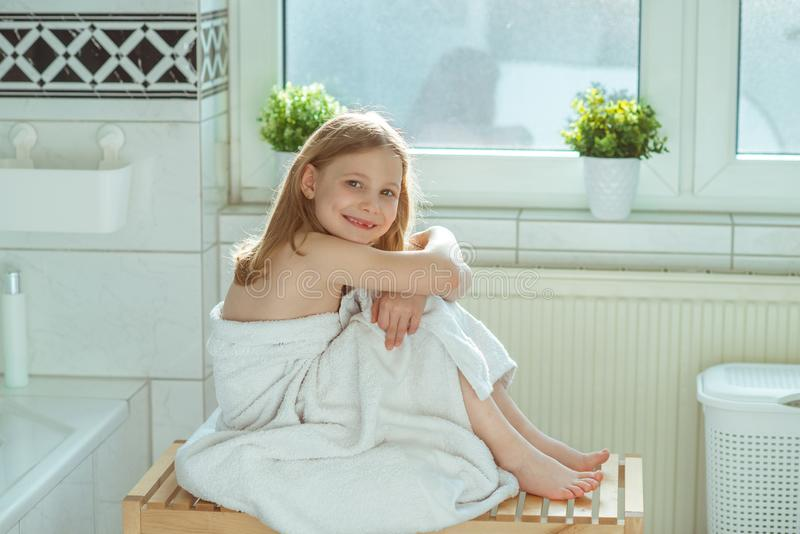 Portrait of pretty little child girl with white towel after show. Er in bright bathroom at home stock photography