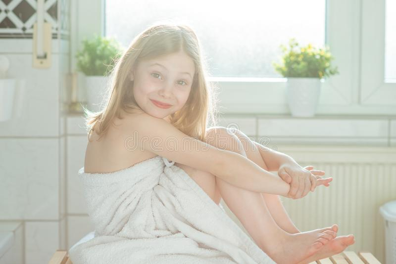 Portrait of pretty little child girl with white towel after show. Er in bright bathroom at home stock photo