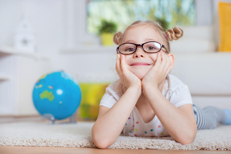 Portrait of pretty little girl on carpet at home with globe on b royalty free stock photo