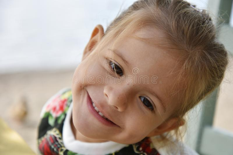 Portrait of a pretty little girl posing outdoors against the background of sea or lake in autumn or winter. Little girl with funny royalty free stock photos