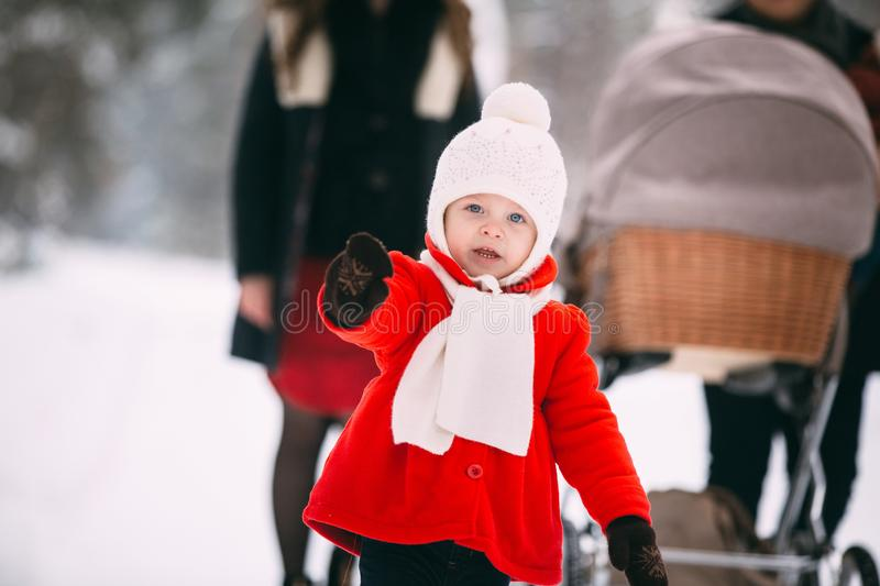Portrait of pretty little girl in red coat enjoying winter day. In the background, her family, mom, dad and little royalty free stock images
