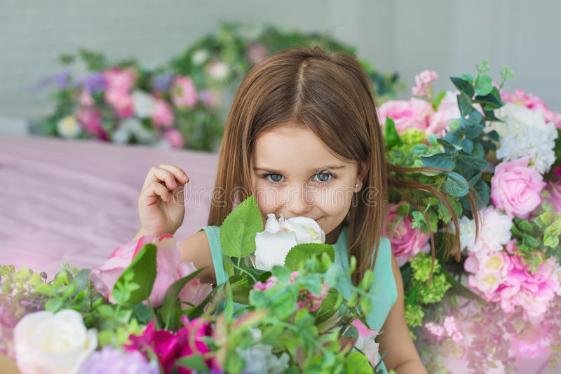 Portrait of a pretty little girl in a turquoise dress sniffs a flowers in a studio stock photo