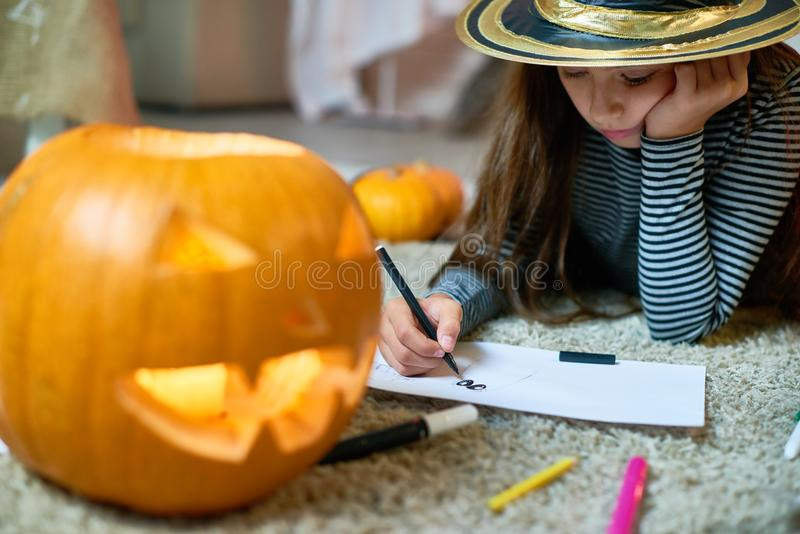 Cute Girl Drawing Halloween Pictures stock photos