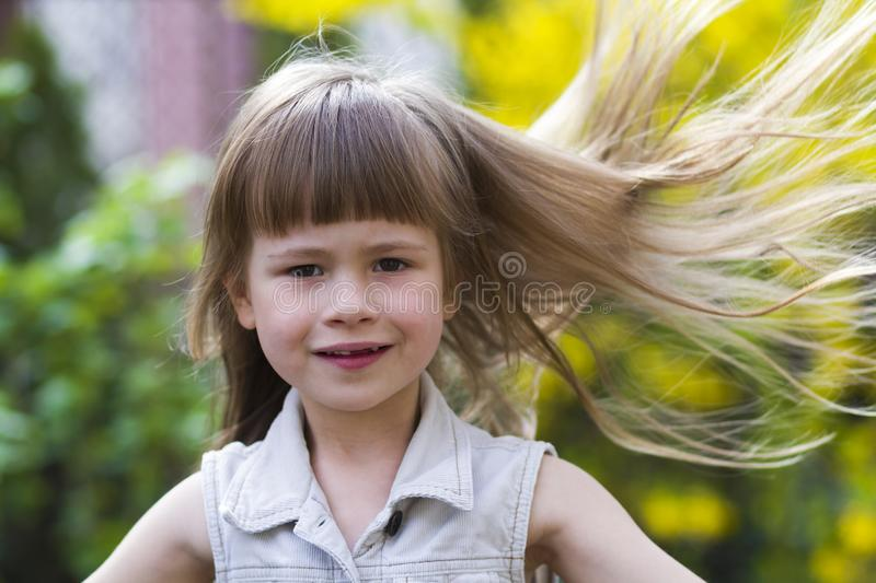 Portrait of a pretty little long-haired blond preschool girl in. Sleeveless white dress smiling shyly into camera against blurred outdoors background. Innocent stock image