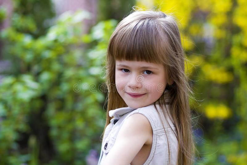 Portrait of a pretty little long-haired blond preschool girl in. Sleeveless white dress smiling shyly into camera against blurred outdoors background. Innocent royalty free stock images
