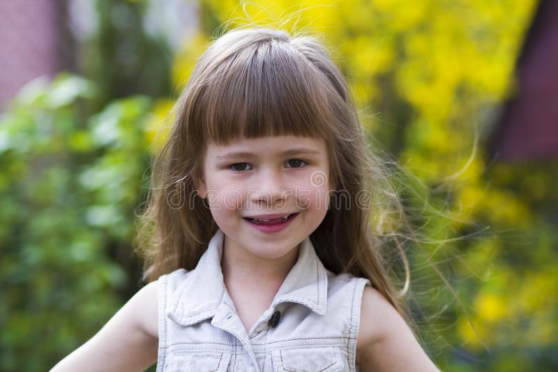 Portrait of a pretty little long-haired blond preschool girl in. Sleeveless white dress smiling shyly into camera against blurred outdoors background. Innocent stock images