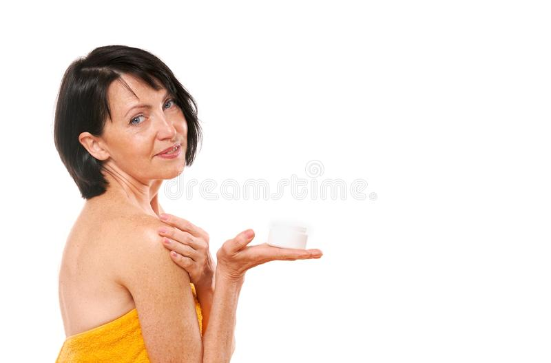 Portrait of pretty mature woman holding face cream on her hand royalty free stock photography