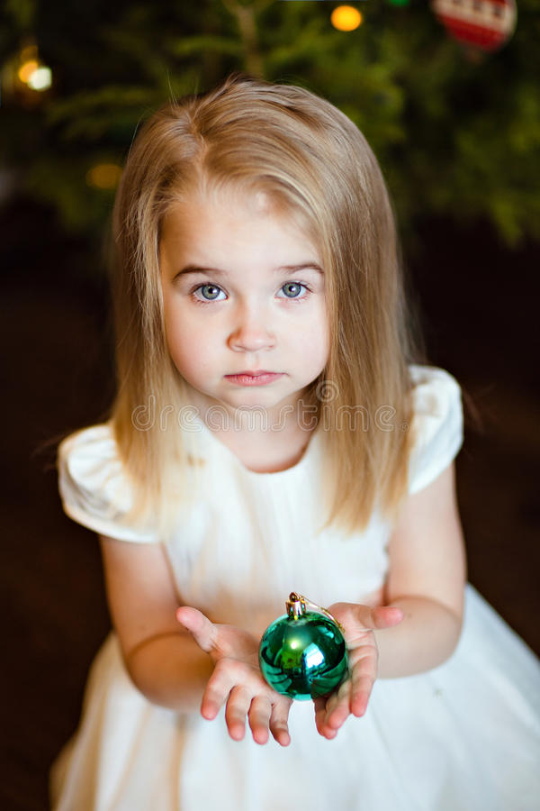Portrait of a pretty serious cute girls baby blonde with straight hair, holding a Christmas ball on the background of Christmas t stock photos