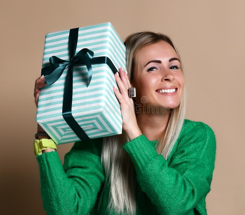 Portrait of a pretty smiling blonde girl holding gift box and looking at it, over color beige background royalty free stock photos