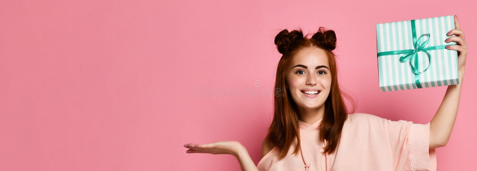 Portrait of a pretty smiling redhead girl holding gift box and looking at it, isolated over color pink background royalty free stock images
