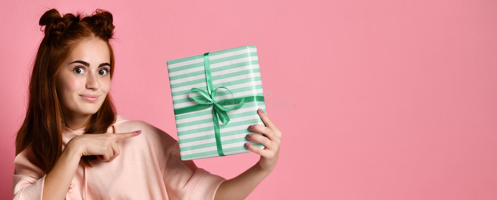 Portrait of a pretty smiling redhead girl holding gift box and looking at it, isolated over color pink background royalty free stock image
