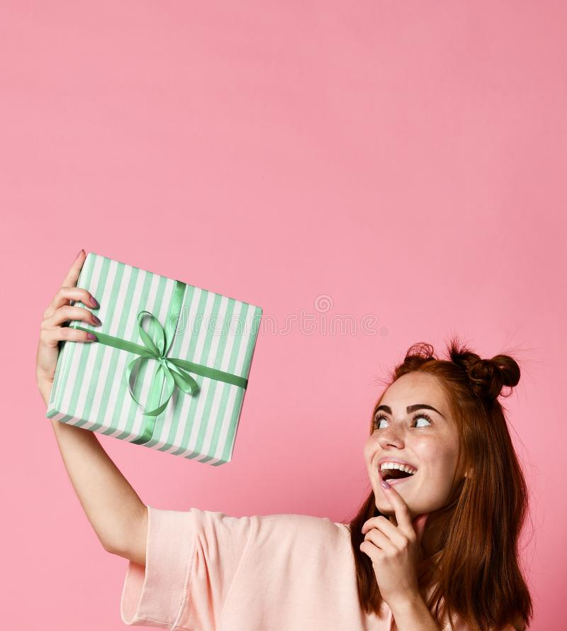 Portrait of a pretty smiling redhead girl holding gift box and looking at it, isolated over color pink background stock image