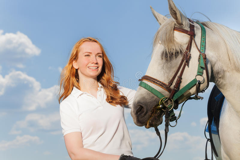 Portrait of pretty smiling woman with white horse royalty free stock image