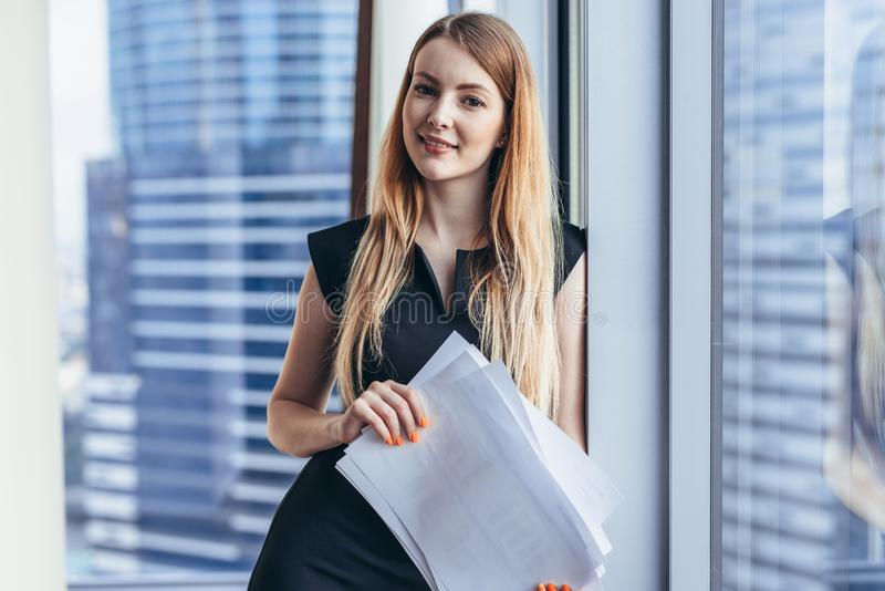 Portrait of pretty smiling young woman holding papers standing at window with cityscape view stock photo