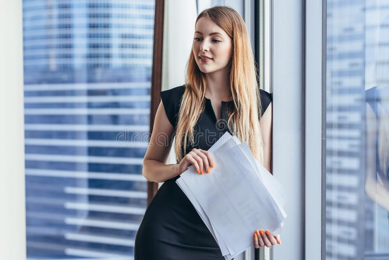 Portrait of pretty smiling young woman holding papers standing at window with cityscape view royalty free stock photos