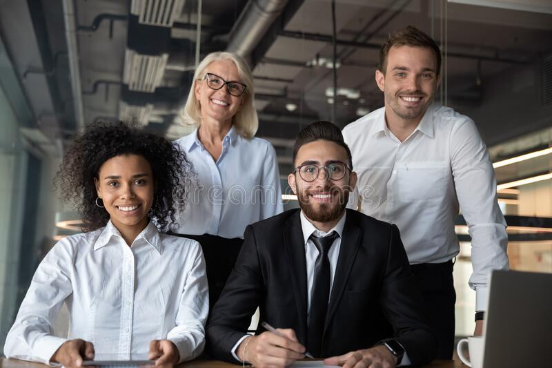 Portrait of pretty successful multi-ethnic corporate close-knit team royalty free stock image