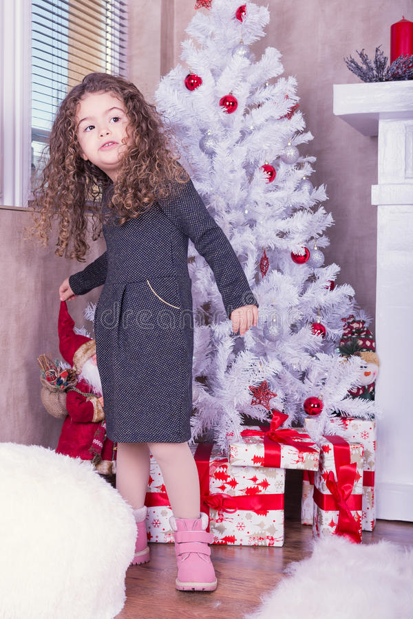 Portrait of pretty sweet little girl near a fireplace in Christmas stock photo