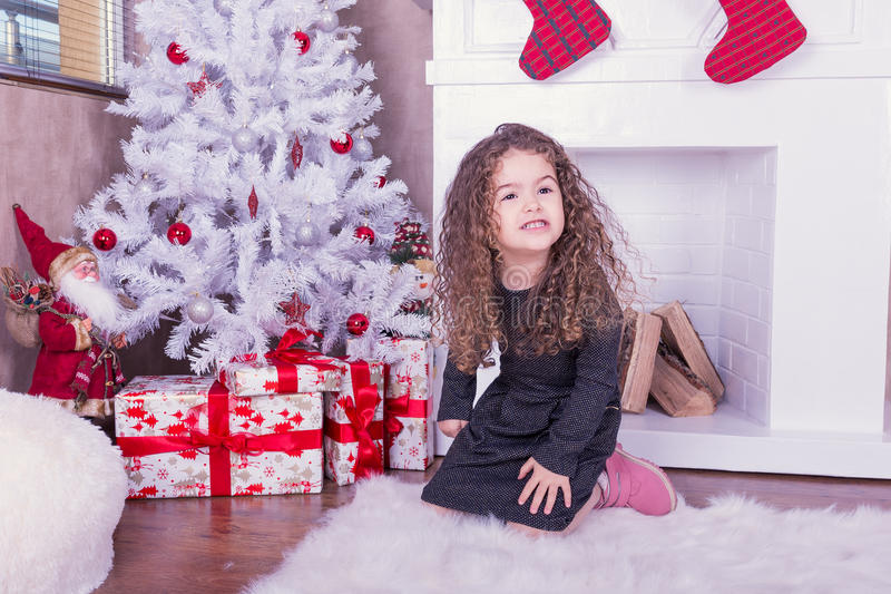 Portrait of pretty sweet little girl near a fireplace in Christmas stock image