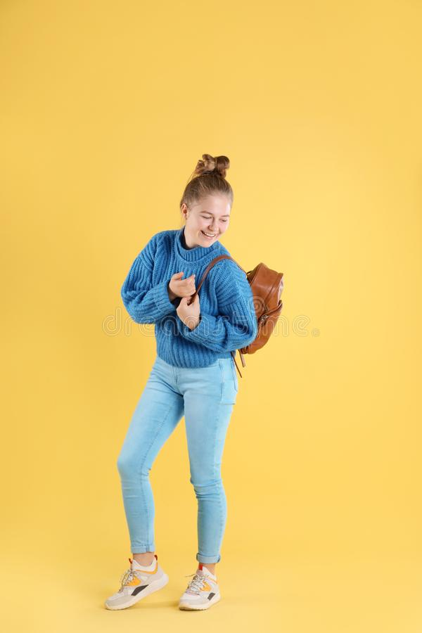Portrait of teenage girl with backpack on color background stock image