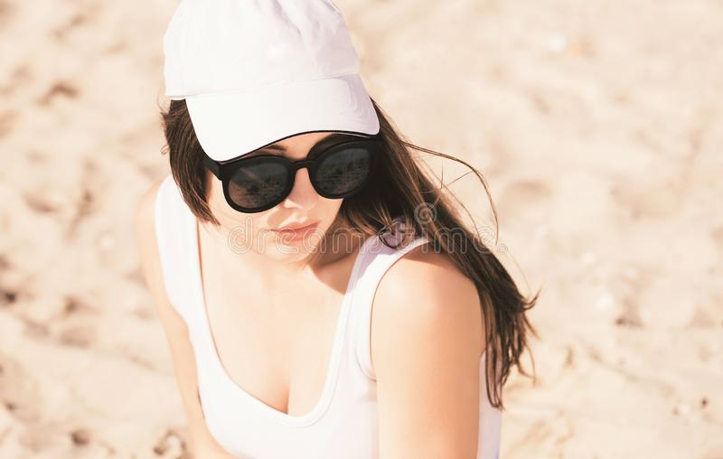 Portrait of a pretty teenage girl with long hair wearing white baseball cap, white swimsuit and trendy sunglasses stock image
