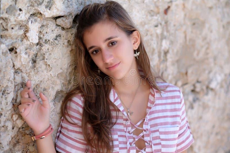 Portrait of a pretty teenage hispanic girl. Romantic portrait of a pretty teenage hispanic girl leaning on a stone wall stock photography