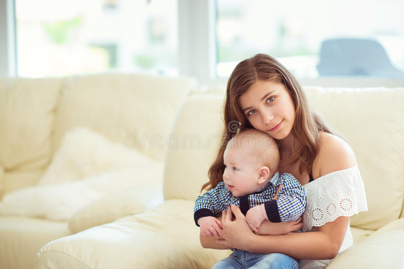 Portrait of pretty teenager girl with her newborn baby stock images