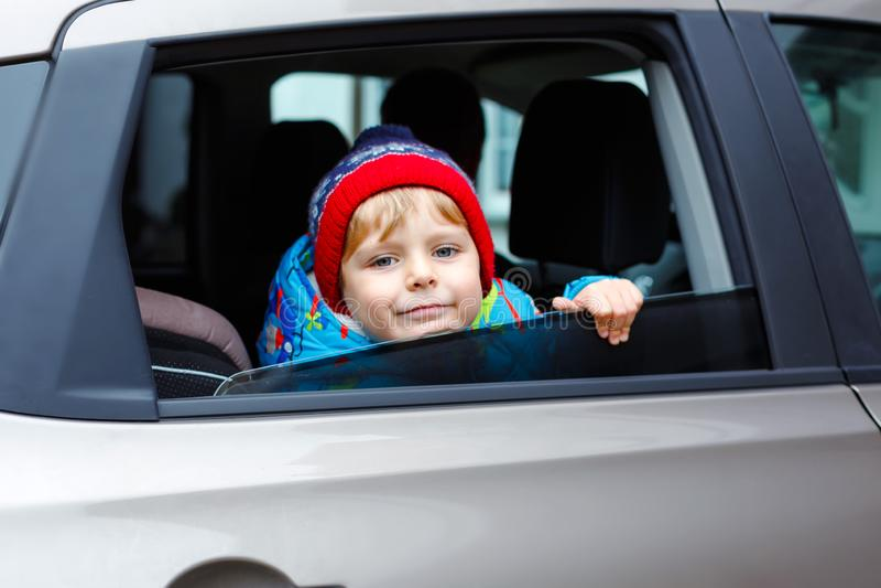 Portrait of pretty toddler boy sitting in car seat. Child transportation safety. Cute healthy kid boy looking happy stock photos