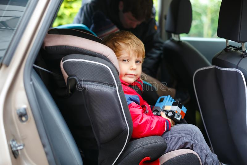Portrait of pretty toddler boy sitting in car seat. Child transportation safety. Father clips on another son on royalty free stock photography