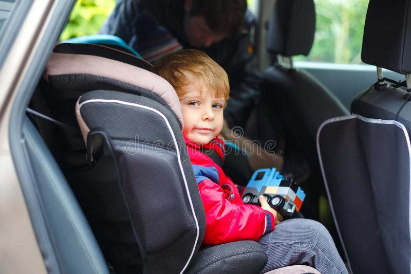 Portrait of pretty toddler boy sitting in car seat. Child transportation safety. Father clips on another son on stock photo