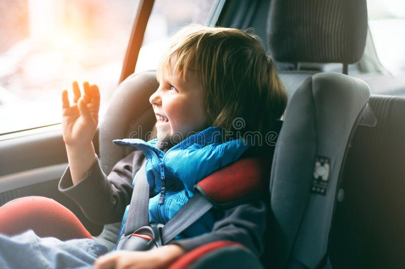Portrait of pretty toddler boy sitting in car seat. Child transportation safety. Sunny day stock image