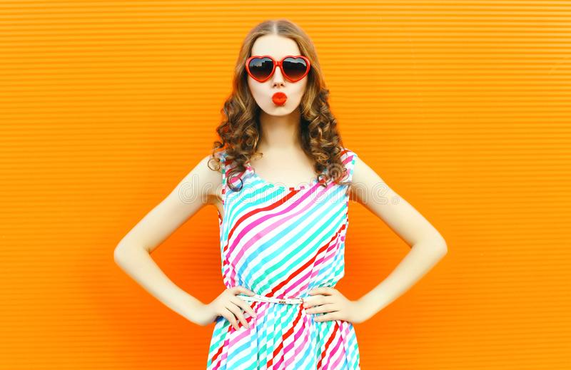 Portrait pretty woman blowing red lips sends sweet air kiss wearing red heart shaped sunglasses, colorful striped dress on orange stock photo