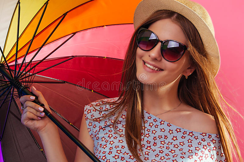 Portrait of a pretty woman with colorful umbrella wearing sunglasses. On pink background royalty free stock photo