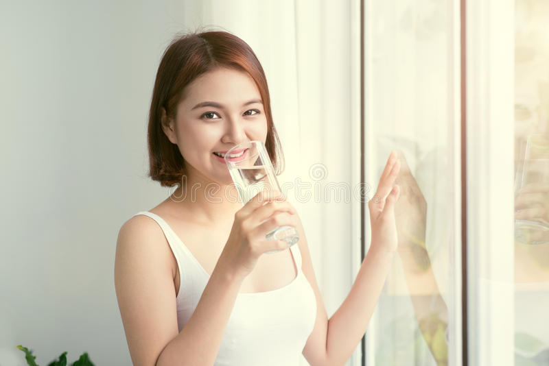 Portrait of a pretty woman holding glass with water. Healthy Lifestyle, Vegetarian Diet And Meal. Drink water. Health Care And Bea. Uty Concept stock photos