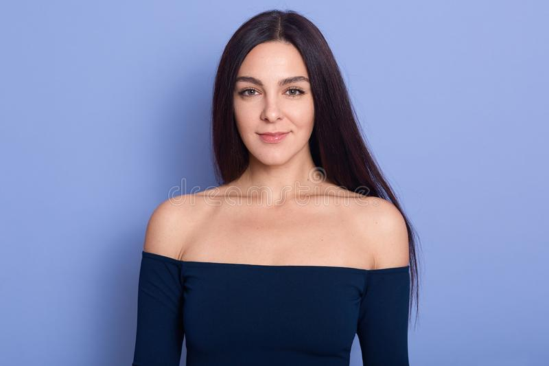 Portrait of pretty woman looking at camera with charming smile, happy girl wearing dark blue dress with bare shoulders, slim royalty free stock photo