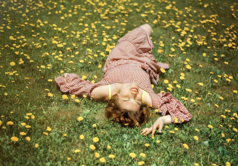 Portrait of pretty woman lying down on dandelions field with closed eyes in red dress. Spring. Allergy and mites in green grass. royalty free stock photo