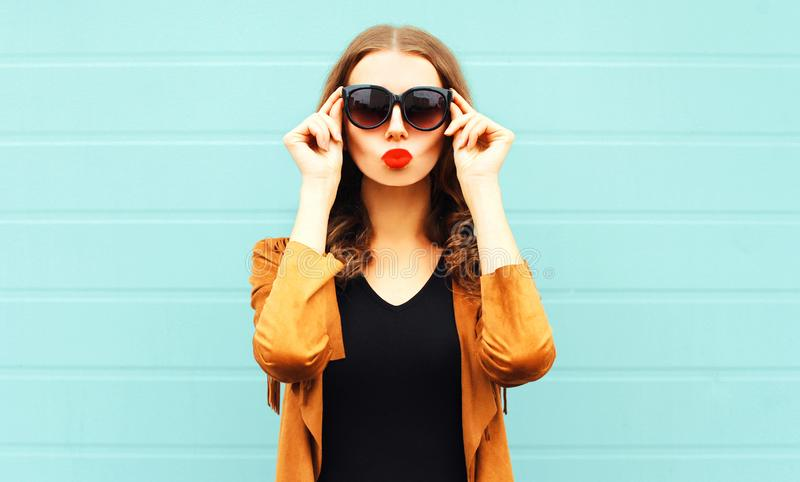 Portrait pretty woman makes air kiss in sunglasses on gray wall royalty free stock photography