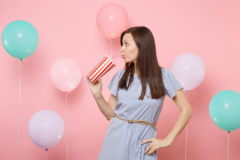 Portrait of pretty woman wearing blue dress looking aside drinking cola or soda from plastic cup on pastel pink. Background with colorful air balloons. Birthday stock photography