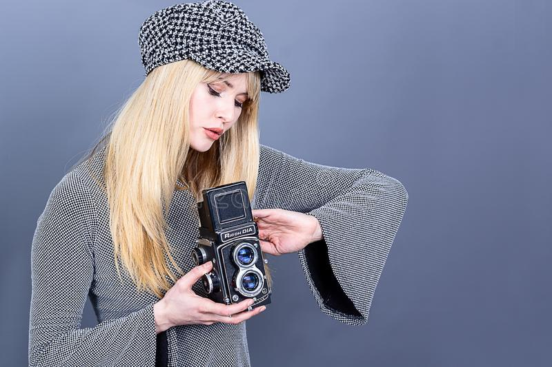 Portrait of an pretty woman wearing 60s fashion look clothes and holding a vintage camera. A pretty woman in 60s style fashion and holding a vintage camera, and stock images