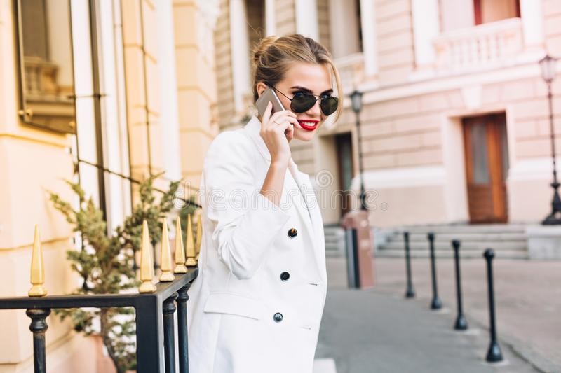 Portrait pretty woman in white jacket and black sunglasses on street. She speaking on phone and smiling with red lips to royalty free stock photos