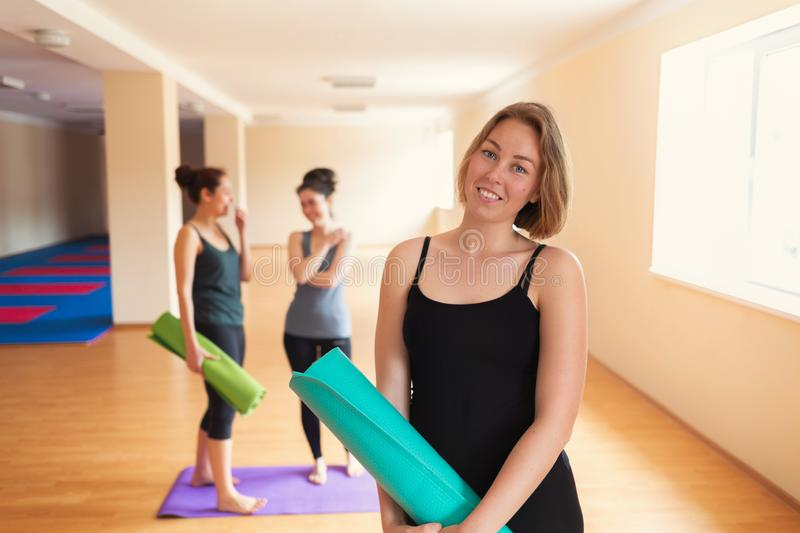 Portrait of pretty woman in yoga class. Group of young women on the background. Tint royalty free stock image