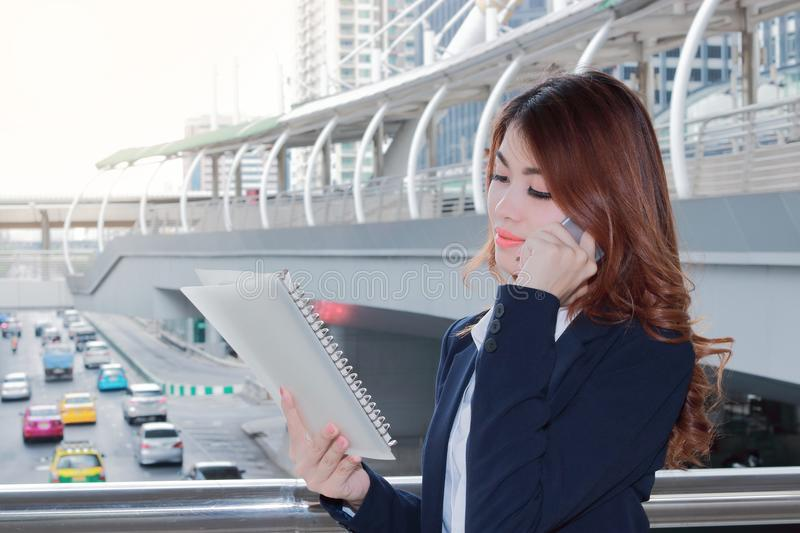 Portrait of pretty young Asian lady secretary talking on phone and looking paperwork in ring binder at urban city with sunshine ef. Fect background royalty free stock photography