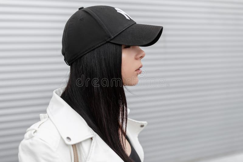Portrait of pretty young beautiful woman in a stylish white leather jacket in a fashionable black baseball cap near a metal wall stock photo
