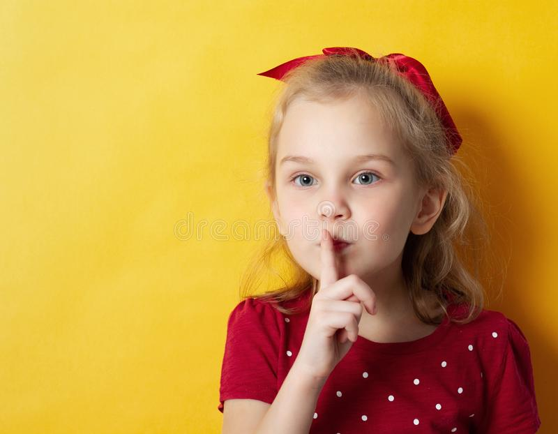 Portrait of a pretty young blonde girl showing silence gesture and winking isolated over yellow background royalty free stock photo