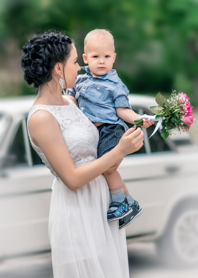 Portrait of pretty young female bride holding small baby boy with wedding roses bouquet at sunny summer park. Mother and her littl royalty free stock photography