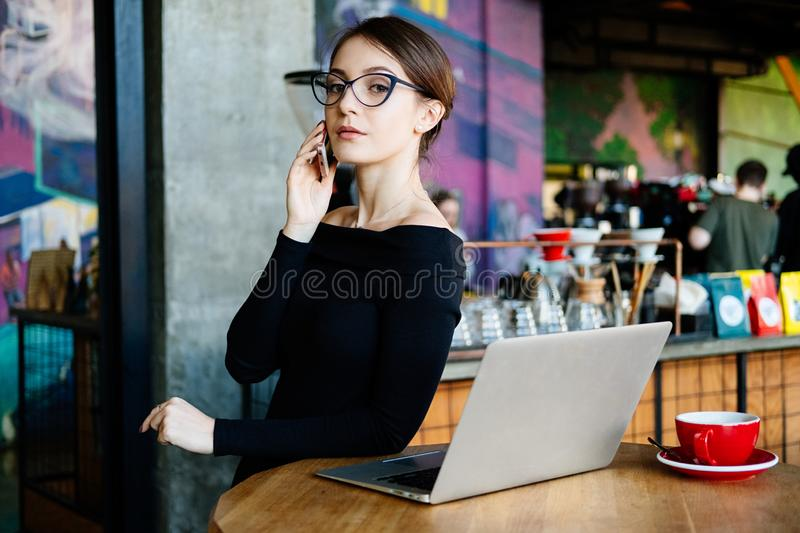 Portrait of pretty young freelancer woman on coffee shop. Beautiful lady with smart phone in her hands using laptop and looking at royalty free stock image