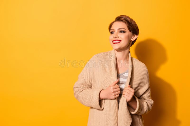 Portrait of pretty young girl with beaming smile dressed in beige cardigan and striped t-shirt isolated on yellow background stock image