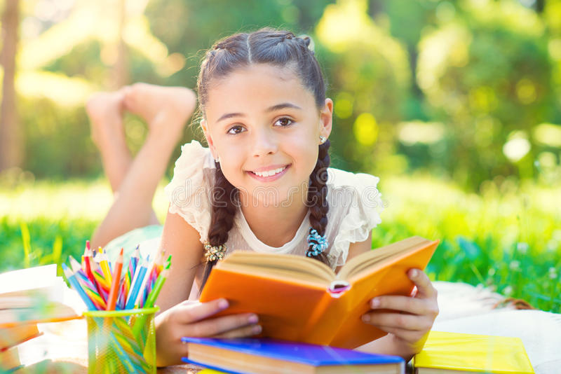 Portrait of pretty young girl reading book in park royalty free stock images