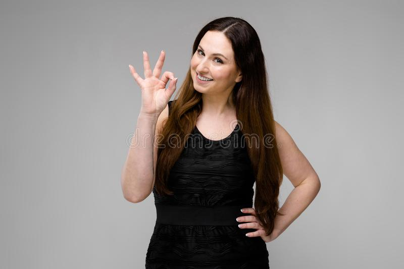 Attractive young positive brunette caucasian smiling woman in black dress showing ok sign isolated on gray stock image