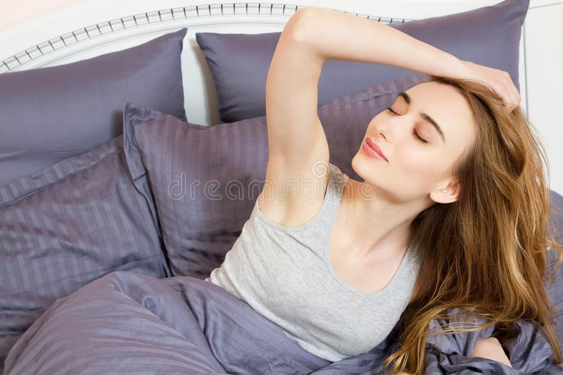 Portrait pretty young white girl on bed in modern apartment in the morning. She keeps eyes closed and looks satisfied. Beautiful. Young woman basking in bed in royalty free stock images